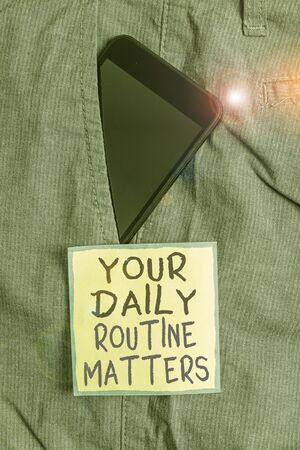 Text sign showing Your Daily Routine Matters. Business photo text practice of regularly doing things in fixed order Smartphone device inside formal work trousers front pocket near note paper
