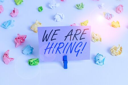 Handwriting text writing We Are Hiring. Conceptual photo recently you employ someone or pay someone to do particular job Colored crumpled papers empty reminder white floor background clothespin Stock Photo