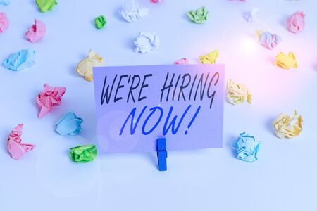 Handwriting text writing We Re Hiring Now. Conceptual photo recently employ someone or pay someone to do particular job Colored crumpled papers empty reminder white floor background clothespin Stock Photo
