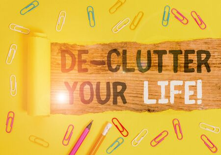 Handwriting text writing De Clutter Your Life. Conceptual photo remove unnecessary items from untidy or overcrowded places Stationary and torn cardboard placed above a wooden classic table backdrop