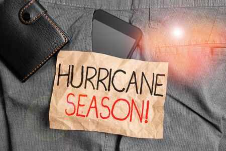 Writing note showing Hurricane Season. Business concept for time when most tropical cyclones are expected to develop Smartphone device inside trousers front pocket with wallet