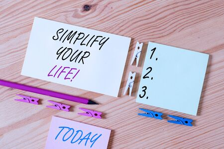 Word writing text Simplify Your Life. Business photo showcasing focused on important and let someone else worry about less ones Colored clothespin papers empty reminder wooden floor background office Foto de archivo - 135562043