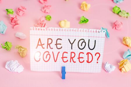 Writing note showing Are You Covered Question. Business concept for asking showing if they had insurance in work or life Colored crumpled papers empty reminder pink floor background clothespin