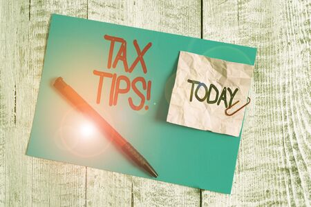 Text sign showing Tax Tips. Business photo showcasing compulsory contribution to state revenue levied by government Wrinkle paper and cardboard plus stationary placed above wooden background