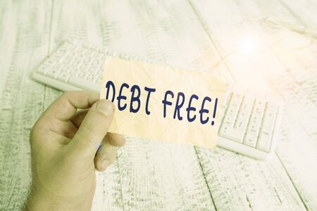 Text sign showing Debt Free. Business photo text does not owning any money or things to any individual or companies man holding colorful reminder square shaped paper white keyboard wood floor