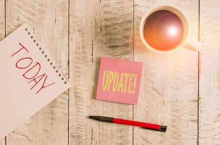 Writing note showing Update. Business concept for make something more modern or up to date like software program Stationary placed next to a cup of black coffee above the wooden table