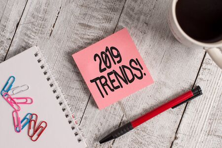 Writing note showing 2019 Trends. Business concept for general direction in which something is developing or changing Stationary placed next to a cup of black coffee above the wooden table