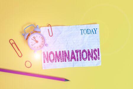 Escritura de texto Word nominaciones. Foto de negocios que muestra la acción de nominar o el estado nominado para el premio Clips de reloj despertador nota aplastada banda de goma de fondo de color de lápiz Foto de archivo