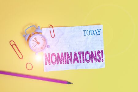 Word writing text Nominations. Business photo showcasing action of nominating or state being nominated for prize Alarm clock clips crushed note rubber band pencil colored background Imagens