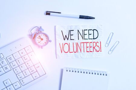 Conceptual hand writing showing We Need Volunteers. Concept meaning someone who does work without being paid for it Copy space on note paper with clock and pencil on the table Banco de Imagens