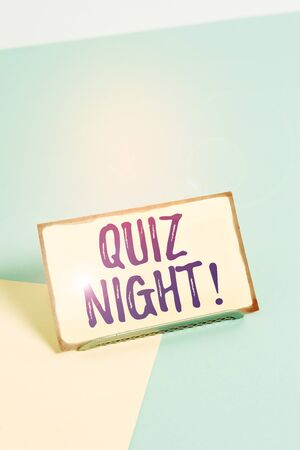 Text sign showing Quiz Night. Business photo showcasing evening test knowledge competition between individuals Paper placed tilted above buffer wire on soft pastel multi colours backdrop