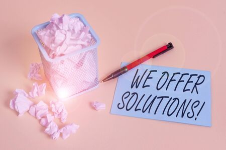 Handwriting text writing We Offer Solutions. Conceptual photo way to solve problem or deal with difficult situation crumpled paper trash and stationary with note paper placed in the trash can 写真素材