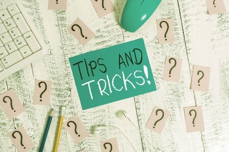 Text sign showing Tips And Tricks. Business photo text means piece advice maybe suggestion how improve Writing tools, computer stuff and scribbled paper on top of wooden table