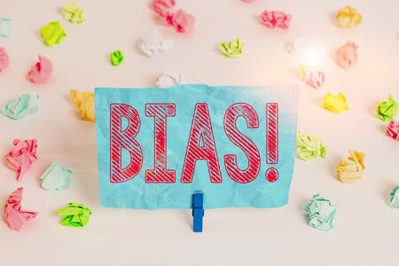 Conceptual hand writing showing Bias. Concept meaning inclination or prejudice for or against one demonstrating group Colored crumpled paper empty reminder white floor clothespin 版權商用圖片
