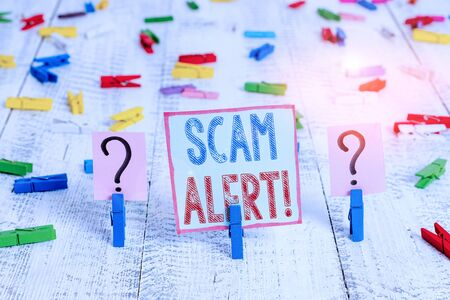 Writing note showing Scam Alert. Business concept for fraudulently obtain money from victim by persuading him Crumbling sheet with paper clips placed on the wooden table