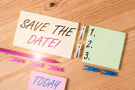 Word writing text Save The Date. Business photo showcasing remember not schedule anything else on this day Colored clothespin papers empty reminder wooden floor background office