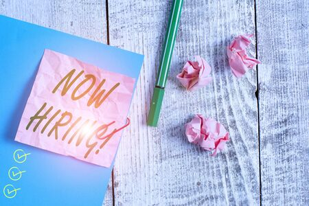 Text sign showing Now Hiring. Business photo text finding evaluating working relationship with future employees Wrinkle paper and cardboard plus stationary placed above wooden background