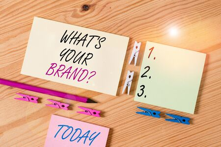 Word writing text What's Your Brand Question. Business photo showcasing asking about product does or what you communicate Colored clothespin papers empty reminder wooden floor background office Foto de archivo