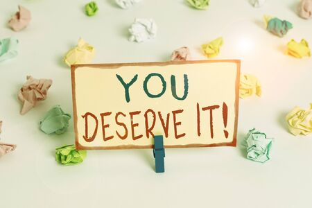 Handwriting text You Deserve It. Conceptual photo should have it because of their qualities or actions Colored crumpled papers empty reminder white floor background clothespin