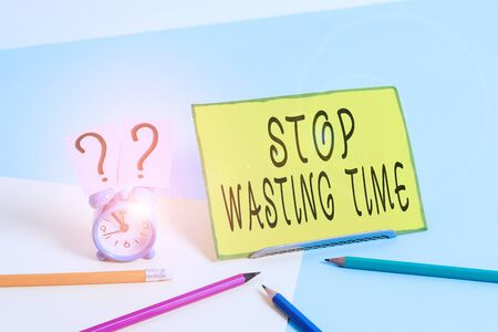 Conceptual hand writing showing Stop Wasting Time. Concept meaning advising demonstrating or group start planning and use it wisely Mini size alarm clock beside stationary on pastel backdrop Stockfoto
