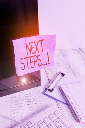 Writing note showing Next Steps. Business concept for something you do after you have finished doing first one Note paper taped to black computer screen near keyboard and stationary