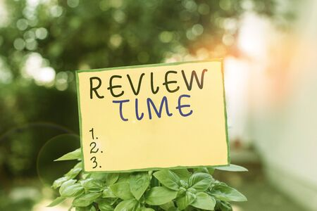 Writing note showing Review Time. Business concept for to think or talk about something again Set schedule to review Plain paper attached to stick and placed in the grassy land