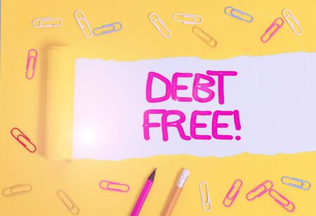 Text sign showing Debt Free. Business photo showcasing does not owning any money or things to any individual or companies Stationary and torn cardboard placed above a plain pastel table backdrop 免版税图像