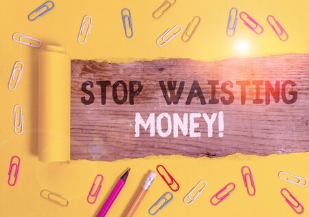 Handwriting text writing Stop Wasting Money. Conceptual photo advicing demonstrating or group to start saving and use it wisely Stationary and torn cardboard placed above a wooden classic table backdrop