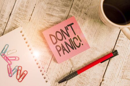 Writing note showing Don't Panic. Business concept for suddenly feel so worried or frightened that you can not behave Stationary placed next to a cup of black coffee above the wooden table