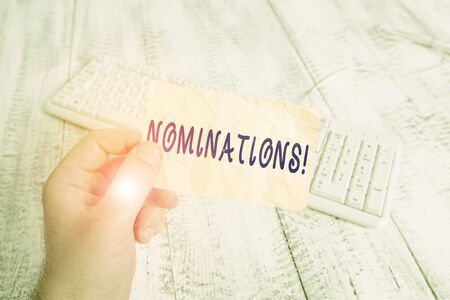 Text sign showing Nominations. Business photo text action of nominating or state being nominated for prize man holding colorful reminder square shaped paper white keyboard wood floor