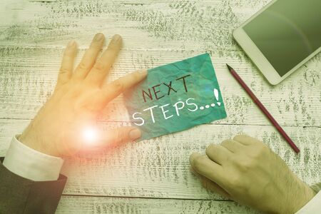 Writing note showing Next Steps. Business concept for something you do after you have finished doing first one Hand hold note paper near writing equipment and smartphone Stockfoto