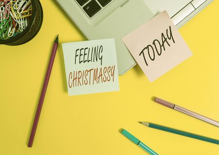 Conceptual hand writing showing Feeling Christmassy. Concept meaning Resembling or having feelings of Christmas festivity Laptop sticky notes container pencils markers colored background