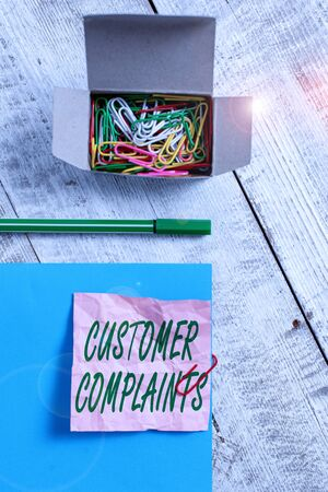 Conceptual hand writing showing Customer Complaints. Concept meaning expression of dissatisfaction on a consumer s is behalf Wrinkle paper and cardboard placed above wooden background
