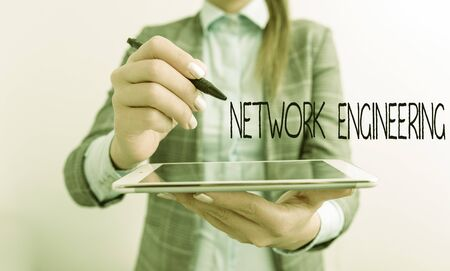 Word writing text Network Engineering. Business photo showcasing field concerned with internetworking service requirement Business woman pointing in empty space with pen and mobile phone