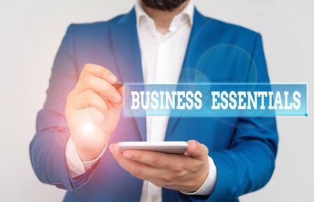 Writing note showing Business Essentials. Business concept for important key ideas to improve business skills Businessman in the blue suite with lap top pointing with finger