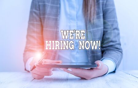 Conceptual hand writing showing We Re Hiring Now. Concept meaning recently employ someone or pay someone to do particular job Business woman sitting with mobile phone on the table