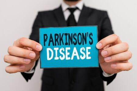 Writing note showing Parkinson S Is Disease. Business concept for nervous system disorder that affects movement Male human wear formal work suit with office look hold book