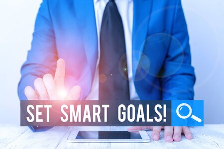 Writing note showing Set Smart Goals. Business concept for list to clarify your ideas focus efforts use time wisely Businessman with pointing finger in front of him