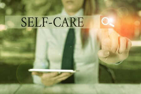 Text sign showing Self Care. Business photo showcasing practice of taking action to preserve or improve ones own health Female business person sitting by table holding mobile phone Stock fotó