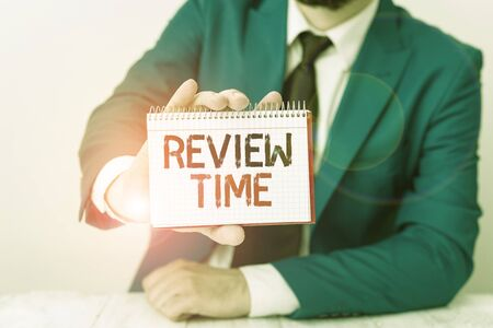 Conceptual hand writing showing Review Time. Concept meaning to think or talk about something again Set schedule to review Man holds empty paper with copy space in front of him Space Stock fotó