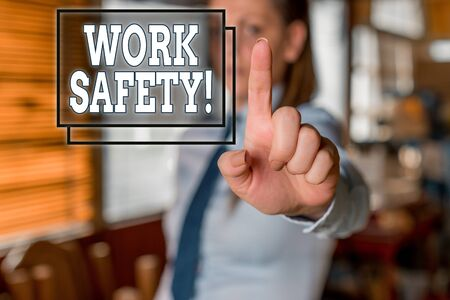 Writing note showing Work Safety. Business concept for policies and procedures in place to ensure health of employees Blurred woman in the background pointing with finger in empty space