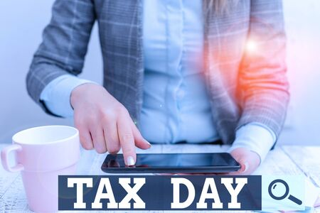 Word writing text Tax Day. Business photo showcasing colloquial term for time on which individual income tax returns Business woman sitting with mobile phone and cup of coffee on the table