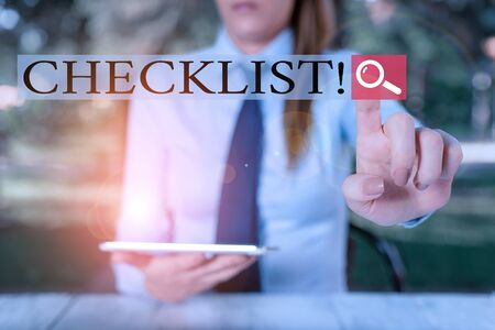 Text sign showing Checklist. Business photo showcasing list items required things be done or points considered Female business person sitting by table holding mobile phone