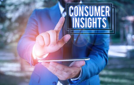 Text sign showing Consumer Insights. Business photo text understanding customers based on their buying behavior Businessman in blue suite with a tie holds lap top in hands
