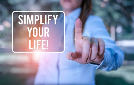 Handwriting text writing Simplify Your Life. Conceptual photo focused on important and let someone else worry about less ones Woman in a blue business shirts pointing with her finger into empty space