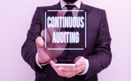 Conceptual hand writing showing Continuous Auditing. Concept meaning Internal process that examines accounting practices Male human wear formal work suit hold smartphone using hand Archivio Fotografico