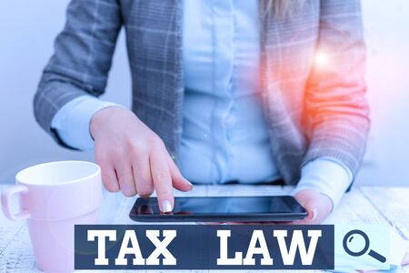 Word writing text Tax Law. Business photo showcasing governmental assessment upon property value or transactions Business woman sitting with mobile phone and cup of coffee on the table
