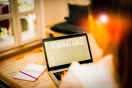 Word writing text Nominations. Business photo showcasing action of nominating or state being nominated for prize woman laptop computer office supplies technological devices inside home Stock Photo