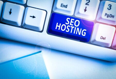 Conceptual hand writing showing Seo Hosting. Concept meaning building website in a way that is friendly for search engines White pc keyboard with note paper above the white background