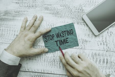 Text sign showing Stop Wasting Time. Business photo text advising demonstrating or group start planning and use it wisely Hand hold note paper near writing equipment and modern smartphone device